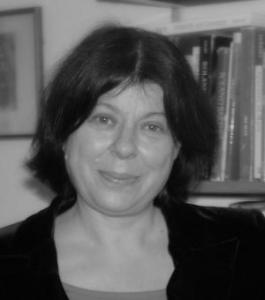 A black and white photo shows a headshot of a woman staring at the camera. She is wearing a black top and is stood in front of a bookshelf.