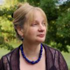 profile of blond-haired woman wearing a sheer black top and dark blue necklace. Trees in background